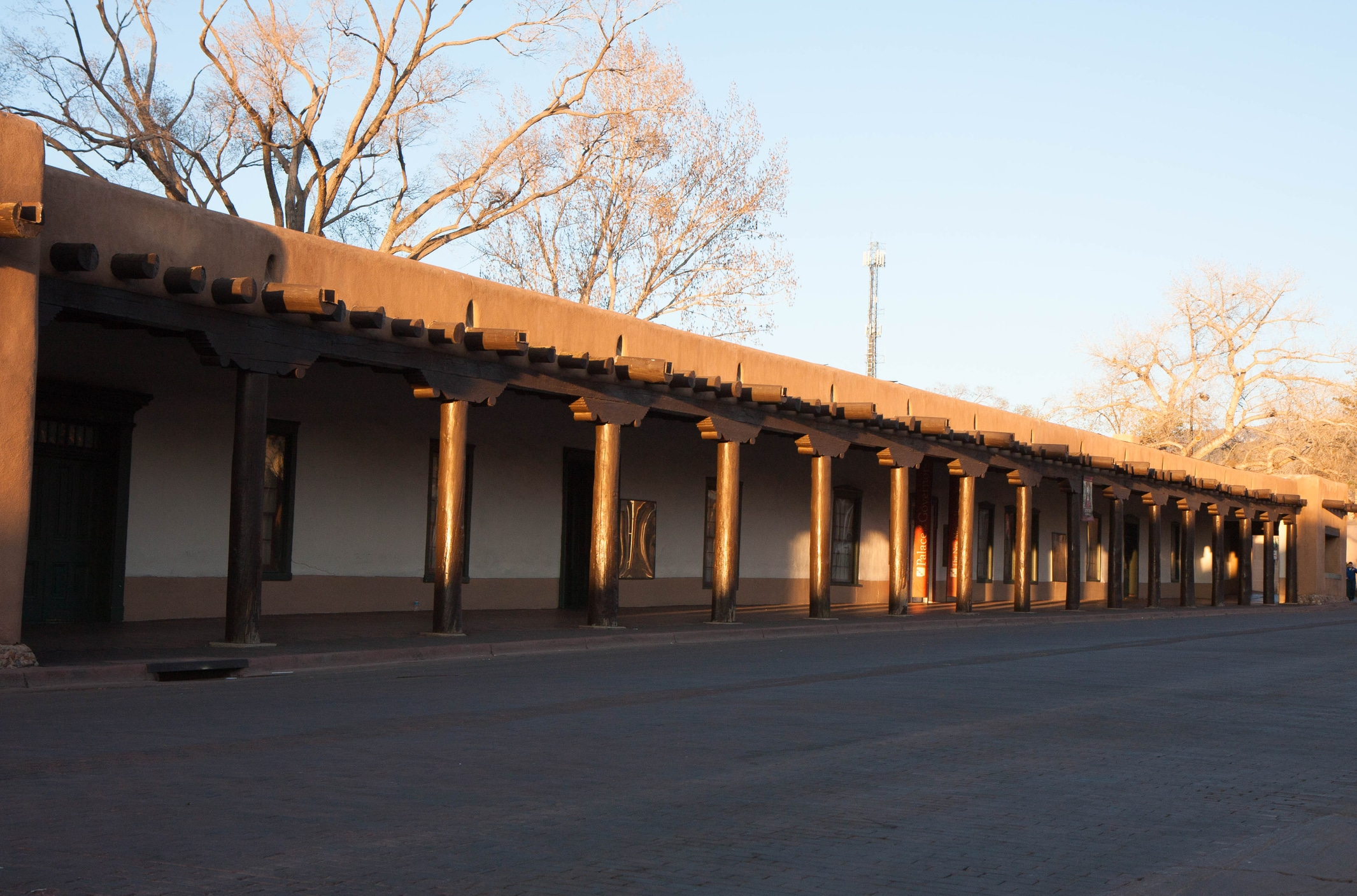 One of the oldest buildings in America, dating back to 1610, the Palace of the Governors hosts a daily Native American Market. Photograph shot at sunset, trees in background, no people visible.