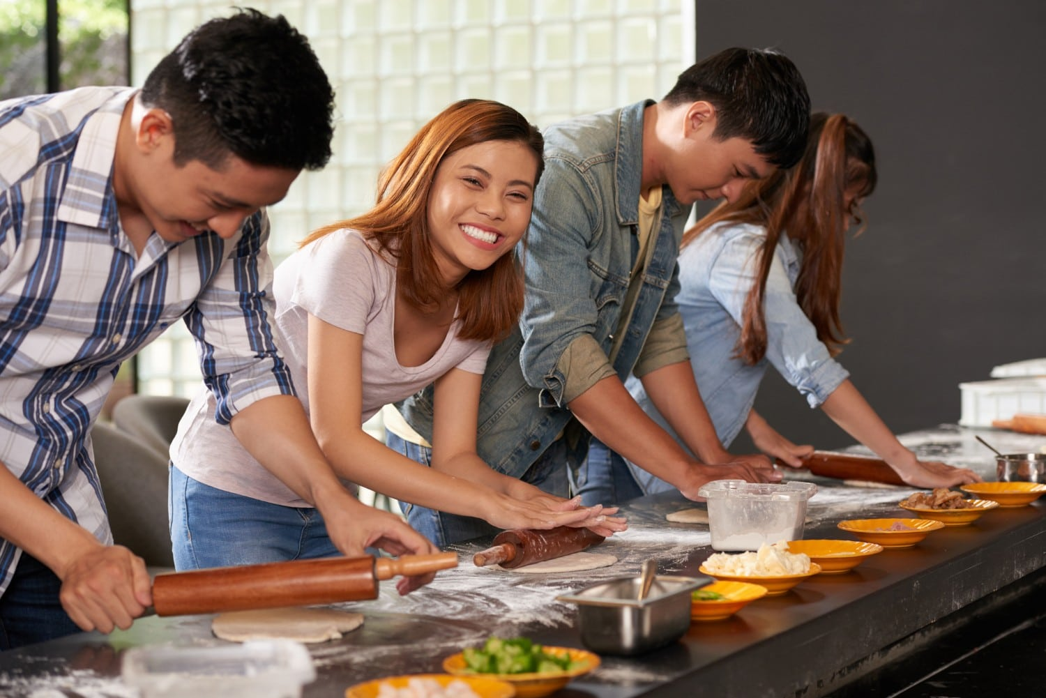 Four people cooking together at a cooking school